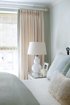 Blue relaxing bedroom features walls clad in blue print wallpaper lined with an iron bed dressed in blue bedding next to a mirrored nightstand and a white glass double gourd lamp placed in front of windows dressed in cream French pleat curtains accented with black and white Greek key trim.