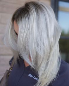 Icy blonde balayage with a deep, ashy shadow root— love the texturized layers that perfectly blend this haircut, only further flattering the color technique.