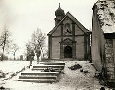 After three days of battle, this town was finally retaken. American troops surrounded the Germans after losing the town to them during an initial counter attack. The patrol is about to enter the the church to examine the belfry and cellar where snipers are still believed to be hiding, where American prisoners were being held. Photographed by Brigadier General Charles Day Palmer