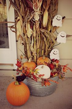 Halloween and fall decorations for the porch.  Galvanized tub with corn stalks, pumpkins and smily ghosts.