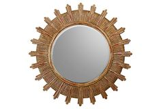"""This 45"""" sunburst has flecks of red paint showing through the gilt on the acacia wood."""