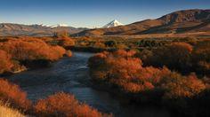 Río Chimehuin, desde ruta a lago Huechulafquen. Al fondo se ve el volcàn Lanín, en la línea de frontera Argentina-Chile. Los arbustos que se ven a la vera del río son sauces mimbre cuyas ramas en otoño e invierno toman su color naranja característico.PH Adriana Boni