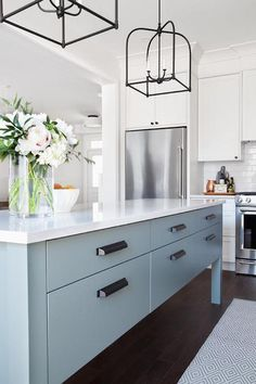 Light fixtures, Beautifully blue and white kitchen features a stainless steel refrigerator recessed beneath off-white shaker cabinets painted in Benjamin Moore Silver Satin. Blue Kitchen Island, Blue Kitchen Cabinets, White Shaker Cabinets, Kitchen Island Decor, Farmhouse Kitchen Decor, Kitchen Interior, White Cupboards, Kitchen Counters, Kitchen Styling
