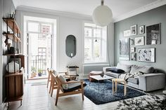Scandinavian apartment living room interior with greyish green walls, black carpet, wooden armchairs, grey sofa, oval mirror and a round white light Living Room Paint, Living Room Interior, Home Living Room, Living Room Designs, Living Spaces, Design Apartment, One Bedroom Apartment, Apartment Interior, Apartment Living