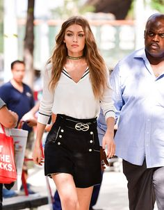 Gigi Hadid in a structured outfit - nautical inspired mini skirt with button detail, and crisp white blouse with black piping, finished with a choker - Gigi Hadid, celebrity street style
