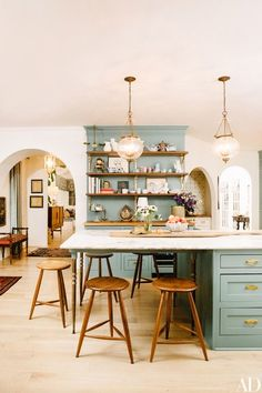 Karen Elson's favorite ceramics by Astier de Villatte fill the shelves in the open kitchen of her Nashville home, with cabinets painted Sherwin-Williams Underseas green | archdigest.com