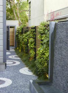 jardin con un muro verde y una cubierta de rocas sobre suelo