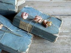 Blue books tied with pink flowers. Lovely vintage feel of well-loved books:)