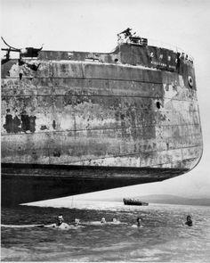 Nov. 11, 1943: Crewmen of a U.S. Coast Guard combat transport go for a swim under the hull of a Japanese landmark in the Solomon Islands dur...
