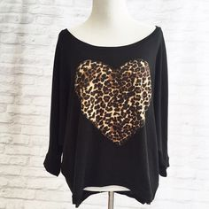 Cheetah Heart Shirt A cute black shirt that can be off the shouldered with a cheetah heart print in the front. In good condition and only been worn once. The arms stop at the elbows. My price is firm. No trades. Forever 21 Tops