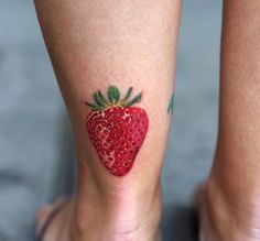 The most realistic Strawberry tattoo we have had the pleasure of seeing, the green on top, the seeds and the light reflections make this strawberry look ready to eat. Done on woman's ankle by Joice Wang, an artist at Bang Bang, New York City.