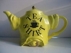 "Tea Shirt teapot in shape of wrinkled tee shirt with handle and spout extending from short sleeves, lettered ""Tea Shirt"" and steaming cup of tea, in black on yellow, ceramic"