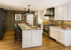 Large kitchen features Shaker white cabinets on long wall and island, and dark birch cabinets in built-in pantry wall