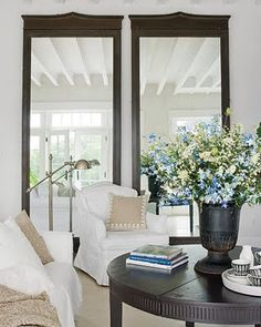 Overscale mahogany mirrors in an all white room with beams + slipcovers + antique weathered wood table makes this coastal chic