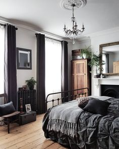 gorgeous details in white bedroom with dark curtains, chandelier, dark grey pintuck bedding, and an iron bed frame. Fireplace in bedroom. Black radiator in bedroom.