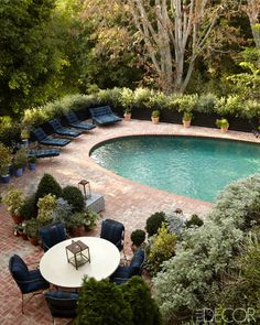 In the pool area, the concrete dining table is by Mecox Gardens, the iron chairs are topped with cushions covered in a Ralph Lauren Home fabric, and the brick pavers are original.   - ELLEDecor.com