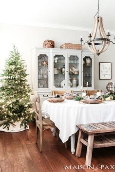 simple green tree and white tablecloth and natural centerpiece make this the perfect farmhouse Christmas dining room and holiday tablescape #holidaytablescape