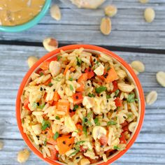 Thai Peanut Rice Bowl Recipe with rice, bell pepper, carrots, peanuts, sesame seeds, cilantro, natural peanut butter, garlic, fresh ginger, teriyaki sauce, tamari soy sauce, Sriracha, lime juice, cilantro, peanut oil