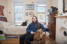 """There are """"dog"""" people and there are """"cat"""" people, and photographer David Williams captures men who identify with the latter group. His project titled Men & Cats began in 2009 as a way to break the stereotype of the """"crazy cat lady"""". Williams photographs guys in their homes and on the street with their feline companion close by. Williams said, """"I wanted to show that regardless of gender, many people have found the joy that cat companionship can bring""""."""