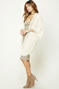 A woven gauze kimono featuring crochet trim throughout, open-front, self-tie straps at neckline, 3/4 sleeves, a high-low hem, and V-cut back.