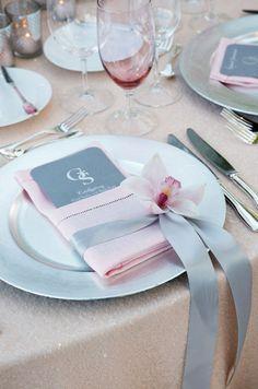 A single pink cymbidium orchid punctuates a slate gray ribbon that wraps around a beautiful pink hemstitch napkin.