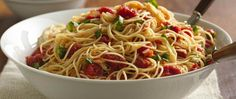 Fresh basil leaves and organic tomatoes dress long thin pasta that's as delish as restaurant fare.
