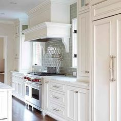 L. Kae Interiors - white beaded kitchen cabinets, gray subway tile backsplash, calcutta gold marble countertop, paneled kitchen hood, kitchen hood corbels, kitchen hood brackets, double door refrigerator, paneled fridge, paneled refrigerator, kitchen wood floors,