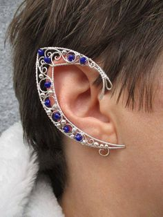 A pair of elf ear cuffs made of silverplated copper wire and dark blue glass beads . The piece is covered by metal protecting laquer. No