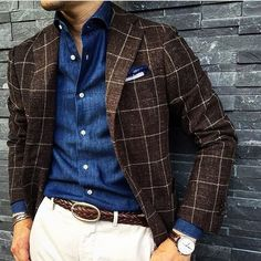 This combination of a dark brown check wool blazer and white chino pants is perfect for a night out or smart-casual occasions. Shop this look on Lookastic: https://lookastic.com/men/looks/blazer-long-sleeve-shirt-chinos/21238 — Blue Chambray Long Sleeve Shirt — White Pocket Square — Dark Brown Check Wool Blazer — Brown Woven Leather Belt — White Chinos
