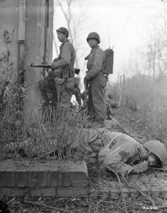 Soldiers of the US 29th Infantry Division take cover after a German sniper has already killed one of their squad, Feb 20, 1945.