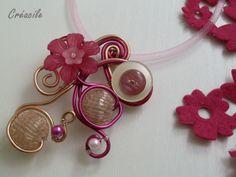 Collier en fil aluminium rose fuchsia et beige saumoné avec différentes perles, des boutons et des fleurs assorties. Le tour de cou est en résille rose clair. Fermé par un fermoir mousqueton et une chaîne d'extension en métal argenté garanti sans nickel et sans plomb.