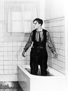 Buster Keaton soaking wet stood up in a bath from One Week.
