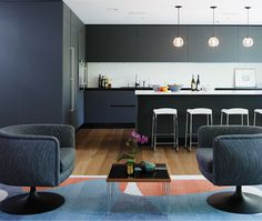 Steel-blue Scavolini cabinetry in the kitchen sets the mood. Oak flooring from Relative Space/Floorworks; armchairs from Hollace Cluny.