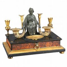 <b>Empire Gilt and Patinated-Bronze, Walnut and Marble Encrier </b> <br /> <i>Circa</i> 1810 <br /> Cast with a kneeling maiden flanked by cornucopia-form sandpot and inkpot and further urn-form candle holders, above a single drawer, on flattened bun feet. <i>Height 9 1/2 inches (23.5 cm), width 12 1/4 inches (31.1 cm), depth 7 1/2 inches (19 cm).</i> <br /> <br /> C