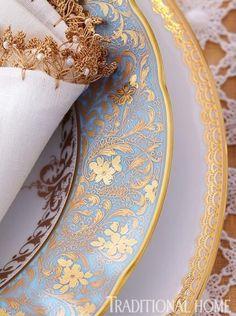 Layered gold scroll dishware.