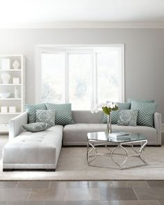 Wondrous light grey tufted sofa with glass top coffee table and white shelves.