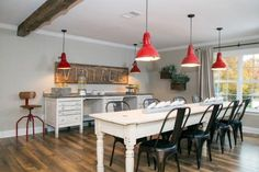 Love the trio of overhead lights (in red) and the awesome narrow and long table