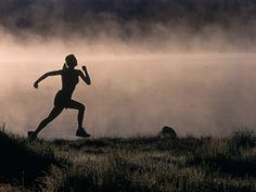 silhouette of woman trail running
