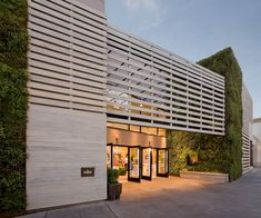 The vertical green wall folds in; the wood slats create a screening; the entry is set back. All of which define a welcoming transitional space between the exterior and interior. Business Architecture, Retail Architecture, Architecture Details, Amazing Architecture, Mall Design, Retail Design, Building Exterior, Building Design, Facade Design