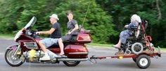 Eine alte Frau ist in ihrem Rollstuhl auf einem Anhänger festgezurrt, der von einem Motorrad gezogen wird. So fahren drei Leute mit Oma durch die Gegend.