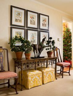 Shapely topiaries studded with small ornaments add a little cheer to this sunroom side table - Traditional Home®
