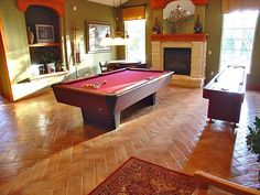 Great pool table and shuffleboard in a chic space. The floors and the fireplace add something special to this room.