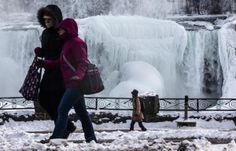 People walk in front of the partially frozen American side of the Niagara Falls during sub-freezing temperatures in Niagara Falls, Ontario on March 3, 2014.