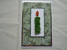 Green quilled candle on white matted rectangle mounted on christmas backing paper