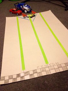 Make-your-own car racing mat and air blown cars. You need: a large piece of cardboard, insulation tape, black and white crayons, matchbox cars, straws, coloured paper cut into triangles and blue tack.
