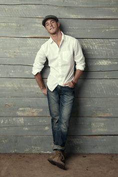 Shop this look on Lookastic: https://lookastic.com/men/looks/long-sleeve-shirt-jeans-desert-boots-flat-cap-bracelet/11180   — Charcoal Flat Cap  — White Long Sleeve Shirt  — Dark Brown Bracelet  — Navy Jeans  — Olive Suede Desert Boots