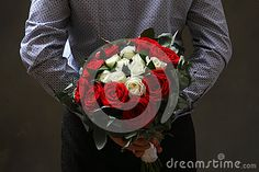 Man holding a rose behind his back
