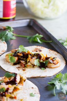 Tacos go Asian in this easy weeknight meal. These Moo Shu Shrimp tacos have shrimp combined with mushrooms, carrots, green onions and cabbage and a simple sauce. The mixture is served in tortillas, topped with hoisin sauce and cilantro.: