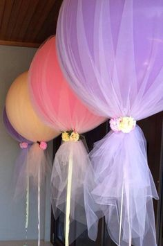 Balloons under tulle - easy decoration for any event! ***This looks super cute but be warned: The tulle is too heavy to actually allow the helium to hold up the balloon, especially if you attach something at the bottom of the balloon. Did these for baby shower and ended up having to pin them- using the tulle in back- to a curtain to make it look like they were floating.****