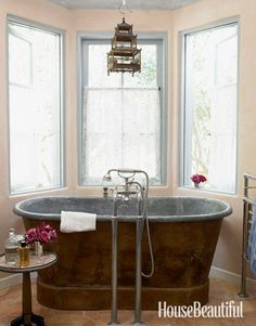 Bathroom Aged to Perfection Antiques and patina dominate the decor in designer Penelope Bianchi's Santa Barbara home. One of her favorite features is this 1860s zinc-lined copper tub, surrounded by a trio of windows. A vintage Chinese birdcage hung from the ceiling adds another element of quirkiness.